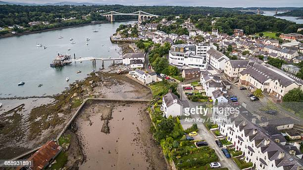 high angle view of residential district by river - menai bridge stock photos and pictures