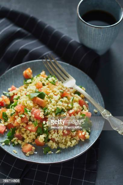 High angle view of rice with chopped tomatoes in plate on napkin