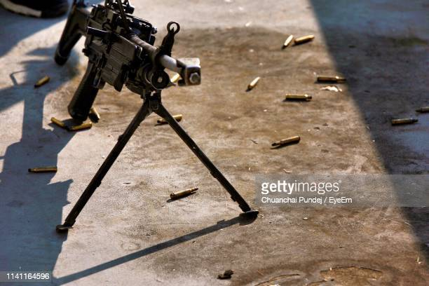 high angle view of rifle on footpath - machine gun stock pictures, royalty-free photos & images