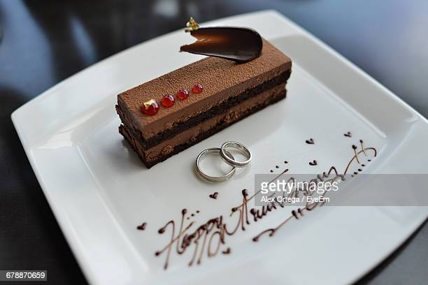 High Angle View Of Rings And Cakes On Plate During Wedding Anniversary