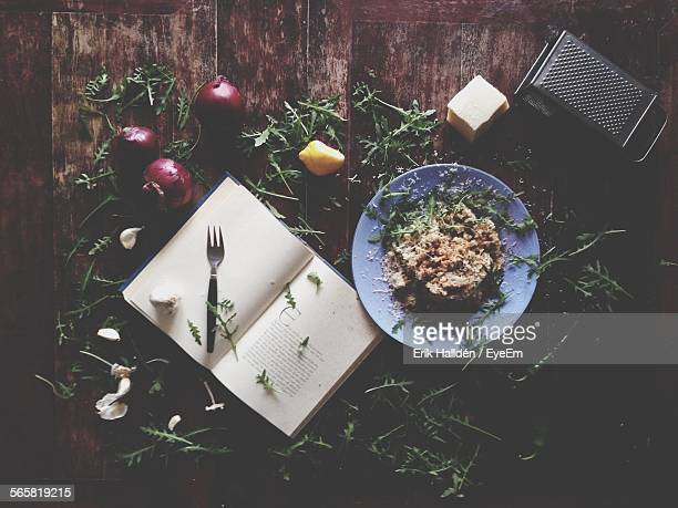 High Angle View Of Risotto And Cookbook With Vegetables On Table