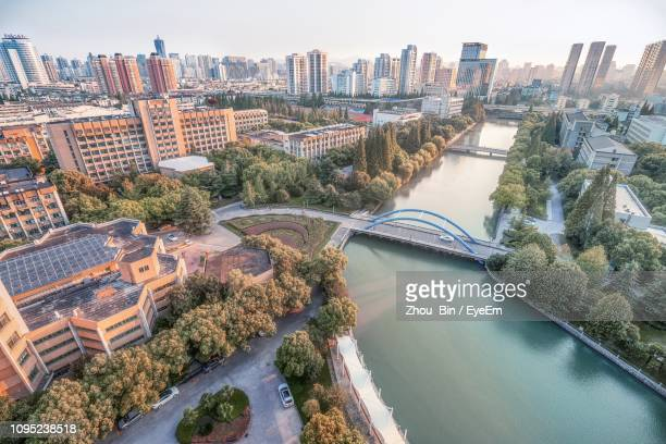 high angle view of river amidst buildings in city - hangzhou foto e immagini stock