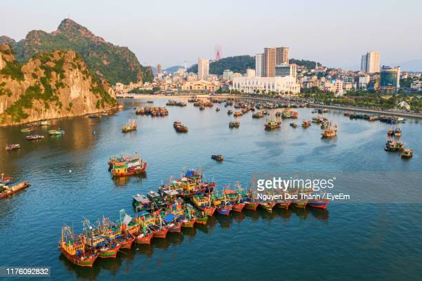 high angle view of river amidst buildings in city - halong bay stock pictures, royalty-free photos & images
