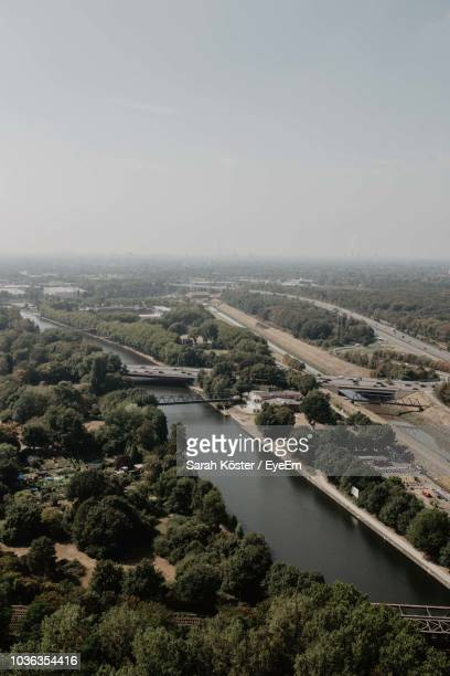 high angle view of river amidst city against sky - oberhausen stock-fotos und bilder