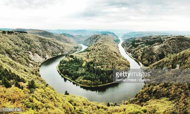 high angle view of river amidst mountains against sky - roman pretot stock-fotos und bilder