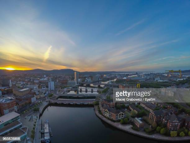 high angle view of river and buildings against sky during sunset - belfast stock pictures, royalty-free photos & images