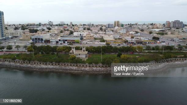 high angle view of river and buildings against sky - ras al khaimah stock pictures, royalty-free photos & images