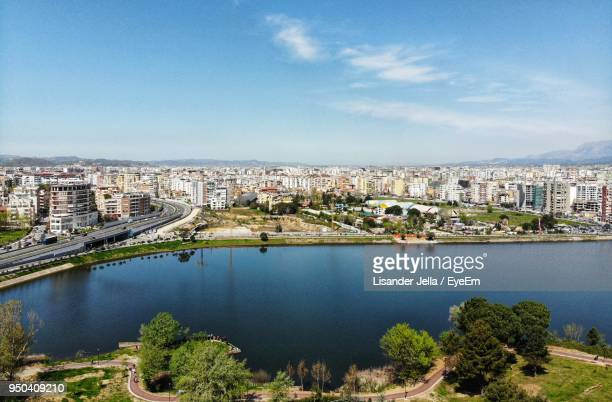 high angle view of river and buildings against sky - albania stock-fotos und bilder