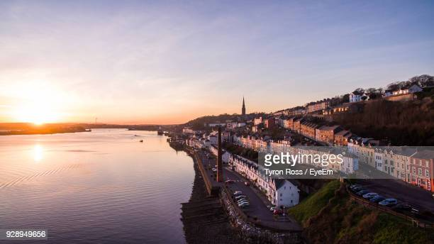 high angle view of river by buildings in town at sunset - county cork stock pictures, royalty-free photos & images