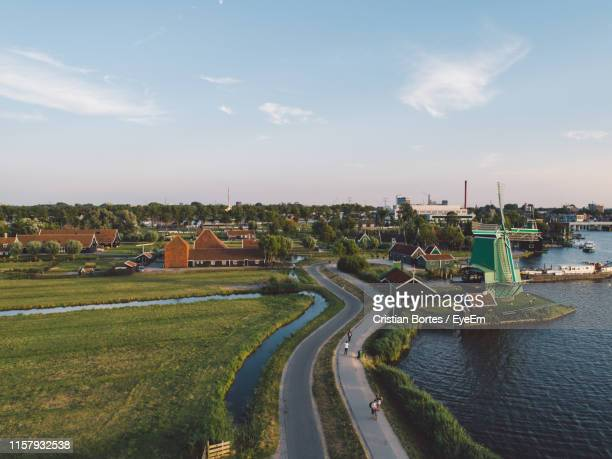 high angle view of river by town against sky - bortes photos et images de collection
