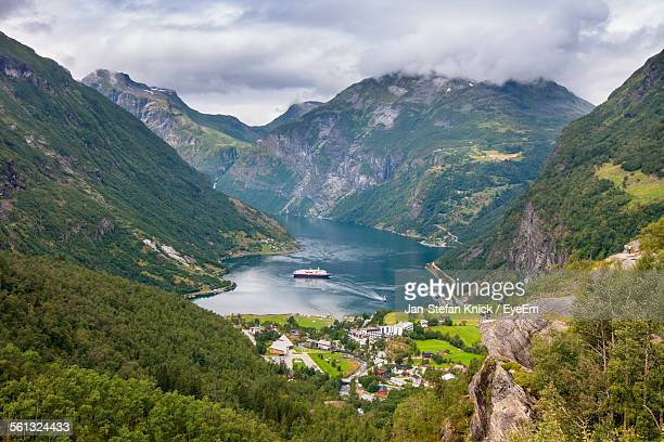 High Angle View Of River Surrounded By Mountains Against Cloudy Sky At Geiranger