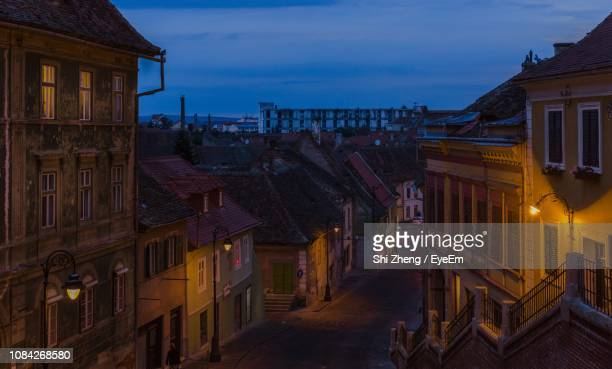 high angle view of road amidst buildings at night - sibiu stock photos and pictures