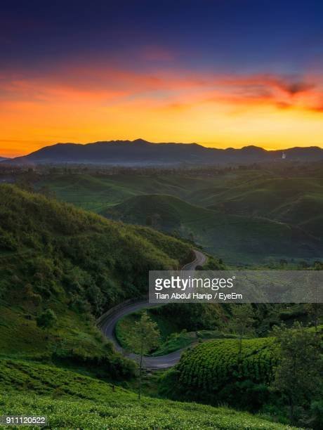 high angle view of road amidst mountains against sky during sunset - tian abdul hanip stock photos and pictures