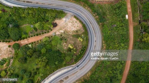 high angle view of road amidst trees - ghana africa fotografías e imágenes de stock