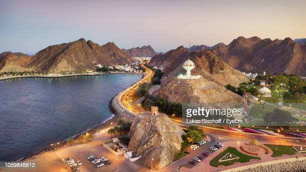 high angle view of road by river and mountains during sunset - oman stock pictures, royalty-free photos & images