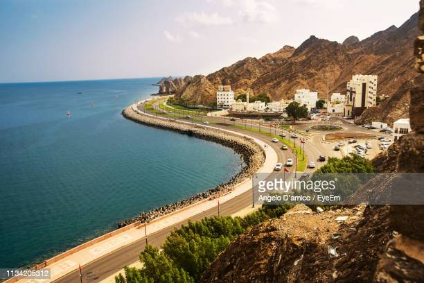 high angle view of road by sea against sky - muscat governorate stock pictures, royalty-free photos & images