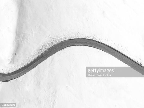 high angle view of road during winter - curve stock pictures, royalty-free photos & images