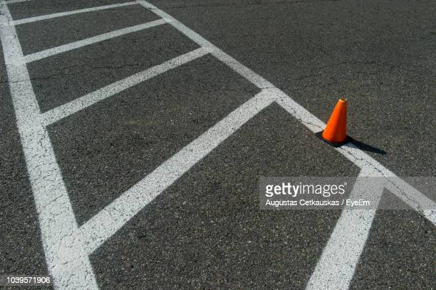 high angle view of road marking and traffic cone on street in city - tracciatura stradale foto e immagini stock