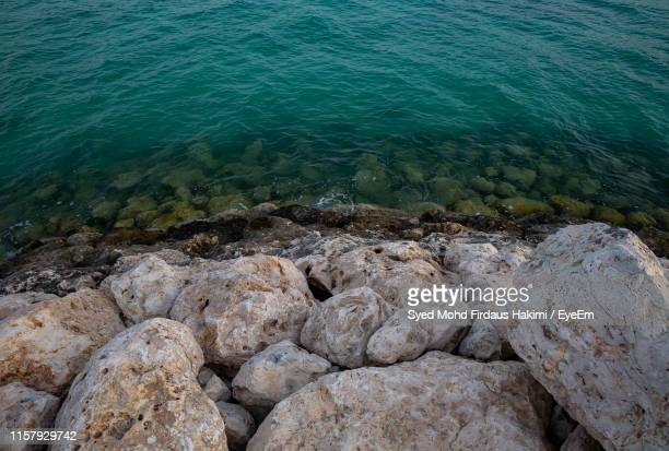 high angle view of rocks at sea shore - hakimi stock photos and pictures