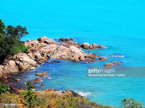 high angle view of rocks by sea against blue sky - sarawak state stock pictures, royalty-free photos & images