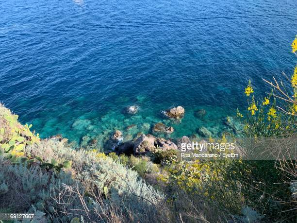 high angle view of rocks by sea - isole eolie foto e immagini stock