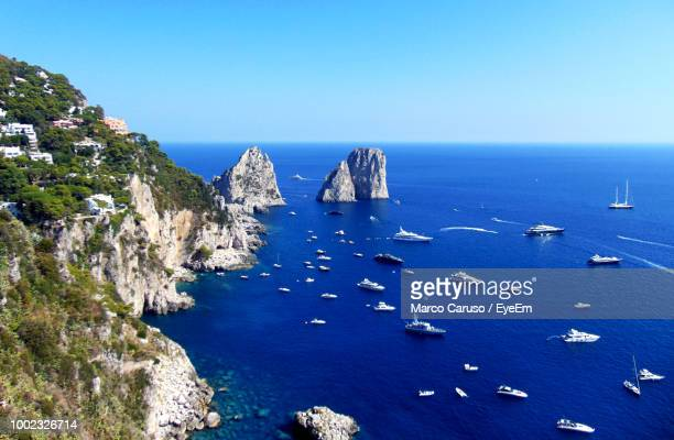 high angle view of rocks in sea against clear blue sky - capri stock pictures, royalty-free photos & images