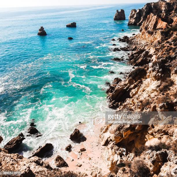 high angle view of rocks in sea - albufeira stock pictures, royalty-free photos & images
