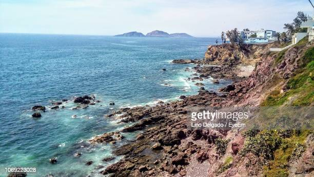 high angle view of rocks on beach against sky - rocky coastline stock pictures, royalty-free photos & images