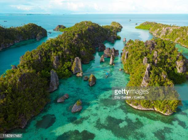 high angle view of rocks on sea - raja ampat islands stock photos and pictures