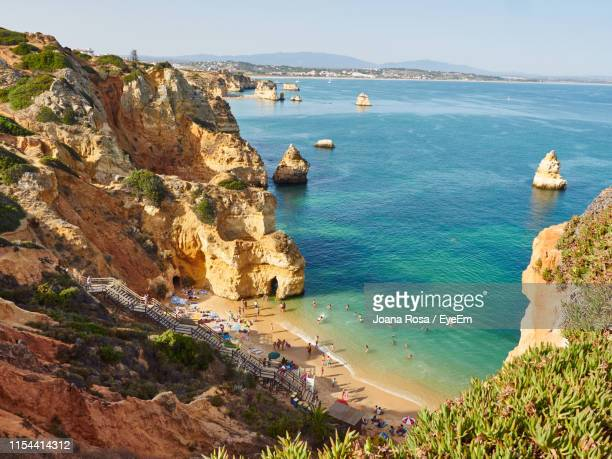high angle view of rocks on sea shore against sky - algarve fotografías e imágenes de stock