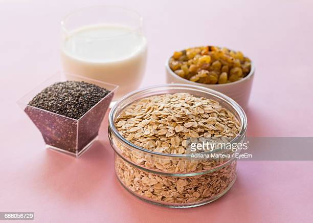 high angle view of rolled oats with raisins and black mustard seeds by milk on pink background - rolled oats stock photos and pictures