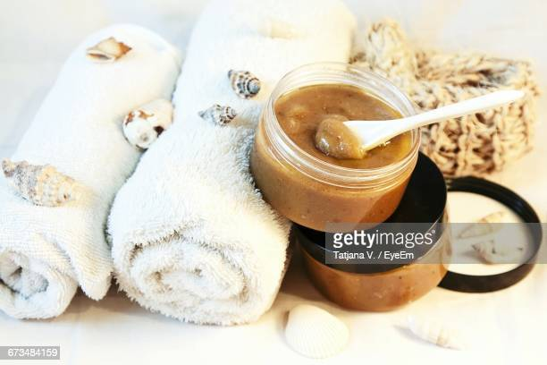 High Angle View Of Rolled Towels And Beauty Products On Table