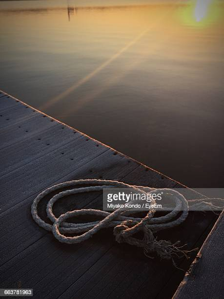 High Angle View Of Rope On Jetty Over Lake During Sunset