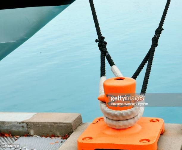 high angle view of rope tied to orange bollard at harbor - bollard stock photos and pictures
