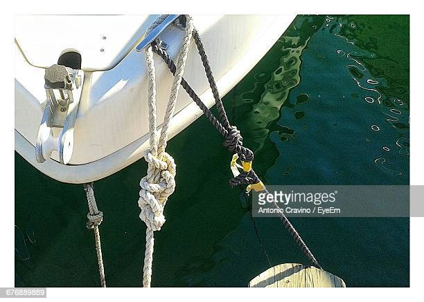 high angle view of ropes tied to boat cleat at lake - vertäut stock-fotos und bilder