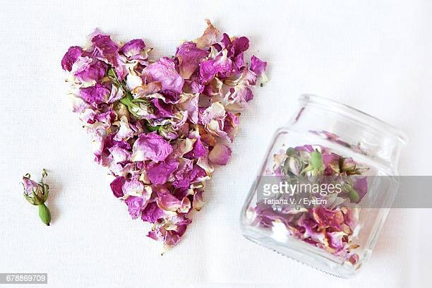 High Angle View Of Rose Hip Petals In Heart Shape By Jar On White Background