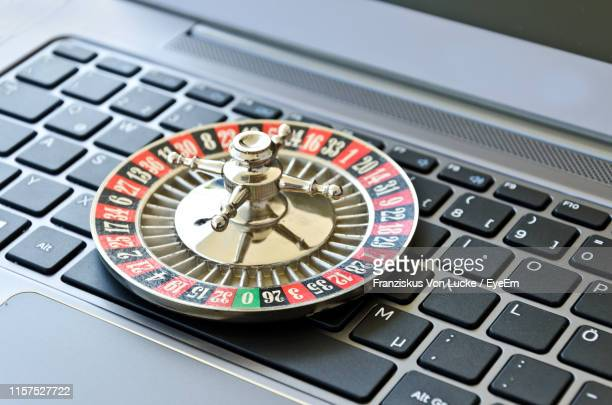 high angle view of roulette wheel on laptop keyboard - 賭け事 ストックフォトと画像