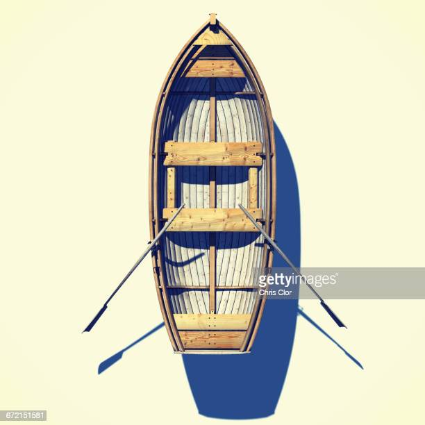 High angle view of rowboat and oars floating in white background