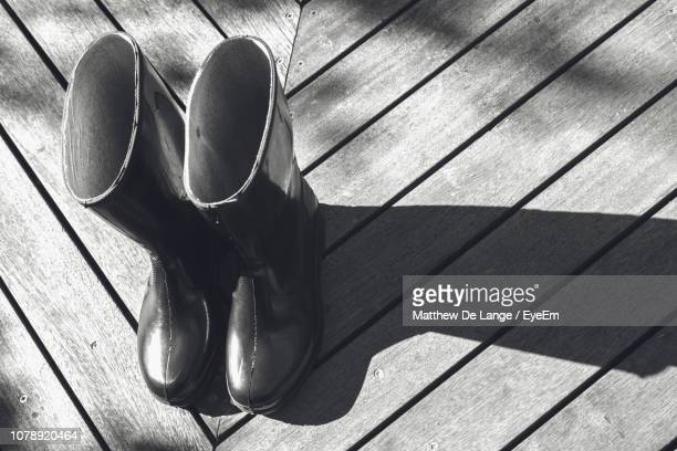 high angle view of rubber boots on wooden floor - レインブーツ ストックフォトと画像