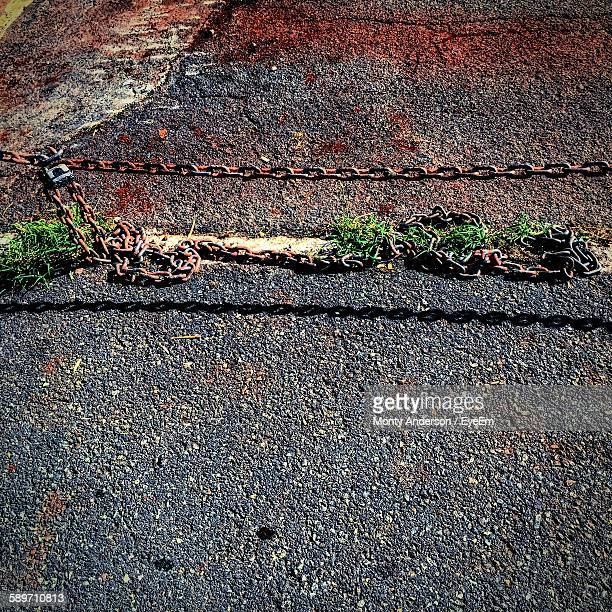 high angle view of rusty chain on ground - monty shadow stock photos and pictures