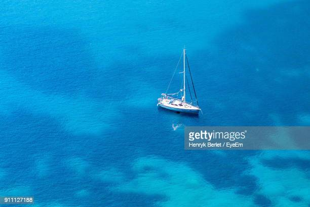 High Angle View Of Sailboat On Sea Against Blue Sky