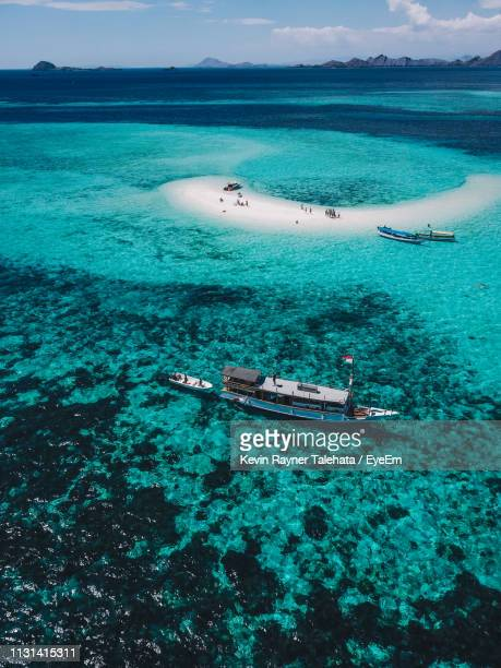 high angle view of sailboat sailing in sea against sky - east nusa tenggara stock pictures, royalty-free photos & images