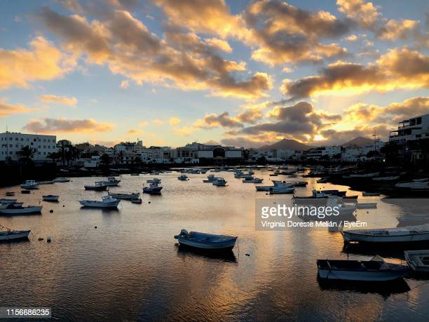 high angle view of sailboats moored at harbor during sunset - arrecife stock photos and pictures