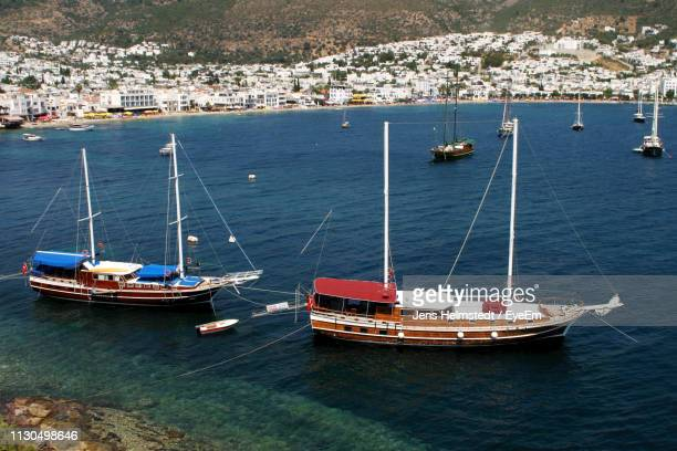 high angle view of sailboats moored in sea - jens helmstedt stock-fotos und bilder