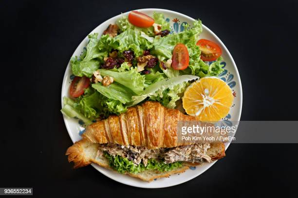 High Angle View Of Salad With Sandwich In Plate On Black Background