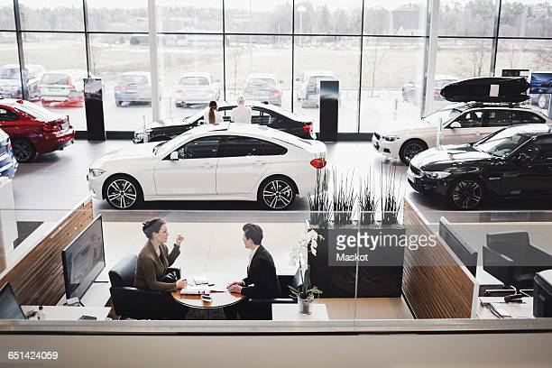 high angle view of saleswoman and customer discussing in meeting at showroom - car dealership stock pictures, royalty-free photos & images