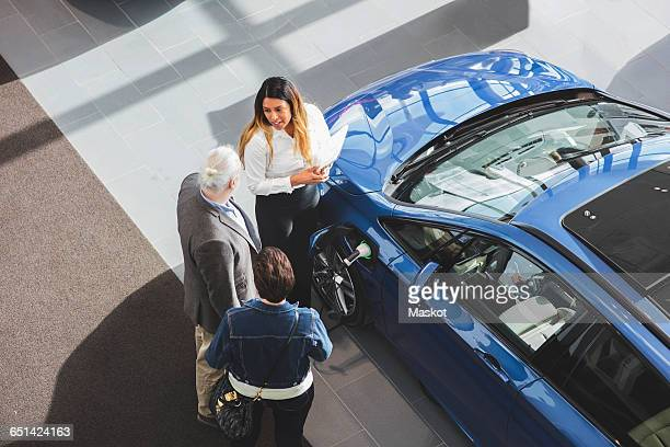 high angle view of saleswoman showing car to customers at showroom - new stock pictures, royalty-free photos & images