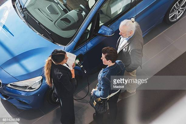 High angle view of saleswoman talking to customers at car showroom
