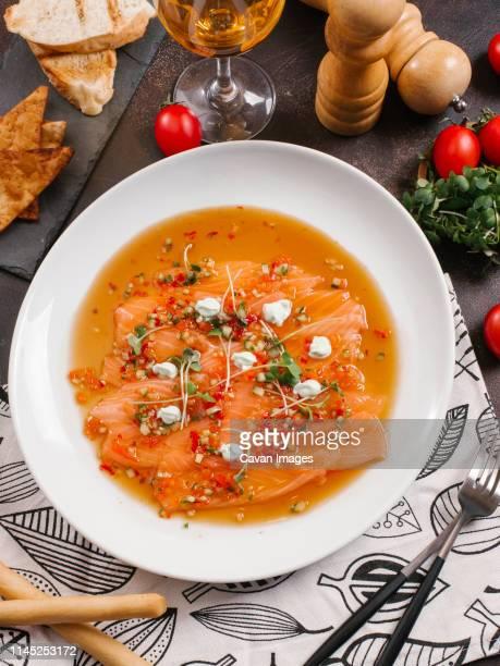 high angle view of salmon carpaccio in plate on table - salmone affumicato foto e immagini stock