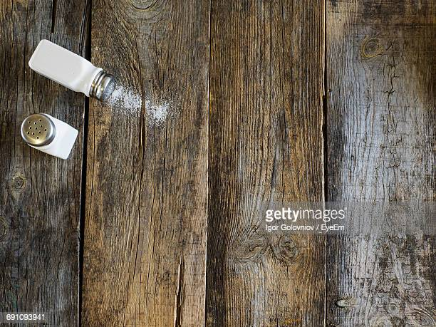 High Angle View Of Salt And Pepper Shakers On Wooden Table